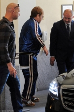 Elton John cuts a dazzlingly casual figure in a sparkling blue tracksuit to visit Donatella Versace in Milan