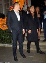 Robbie Williams looks sharp in a black coat and leopard-print shirt as hits the town with pals David Walliams