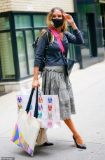 Sarah Jessica Parker looks sweet in a grey midi skirt as she lends a hand