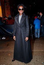 Lupita Nyong'o dons chic black floor-grazing coat while arriving