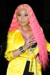 Nicki Minaj flashes her chest under a furry pink jacket as she gives fans