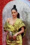 Rihanna spills out of her plunging golden gown as she turns