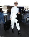 Adriana Lima makes sweats chic as she pairs an all white look with black heeled booties...
