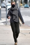 Emma Roberts bundles up with a large scarf and protective face mask