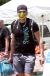 Joel McHale rocks a funny face mask while doing some shopping at a farmer's market as he opens