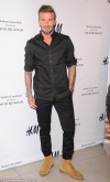 David Beckham looks dapper in a black dress shirt with the sleeves rolled