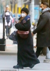 Ashley Olsen bundles up in full-length black overcoat and knit beanie as she