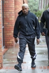 Kanye West braves stormy Los Angeles weather to face