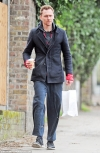 Tom Hiddleston cuts a scruffy figure in hoodie and holey tracksuit