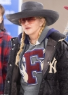 Madonna rocks dapper hat and blonde pigtails as she heads through JFK