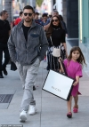 Scott Disick's daughter Penelope, six, waltzes out of Gucci store with gift bag while wearing