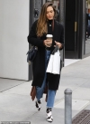 Jessica Alba bundles up in a black duster and jeans with cow print boots
